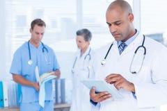 Doctor atento que usa el suyo tableta Fotografía de archivo
