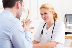 Doctor atractivo joven que escucha su paciente Imagen de archivo libre de regalías