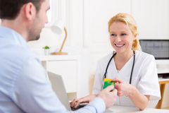 Doctor atractivo joven que toma la tarjeta del seguro médico Fotografía de archivo libre de regalías