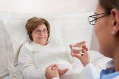 doctor att ge läkarbehandlingen den patient pensionären till Arkivbild