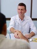 Doctor att uppröra händer till den gammala sjuka mannen i klinik Arkivbilder