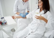 Doctor attaching intravenous drip on lady hand while she drinking water