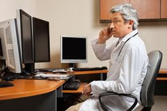 Doctor Attending Phone Call At Clinic Stock Images
