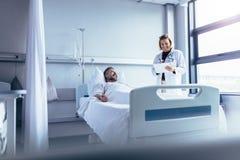 Doctor attending sick patient in hospital bed. Female doctor talking to male patient in hospital bed. Smiling doctor with clipboard attending sick men in Stock Photos