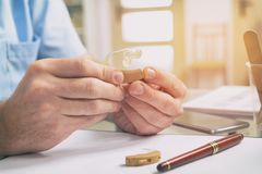 Doctor holding hearing aid Royalty Free Stock Photos