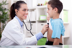 Doctor auscultating a child with a stethoscope in examination ro Royalty Free Stock Photography