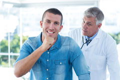 Doctor auscultating his patients back Royalty Free Stock Photos