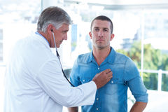 Doctor auscultating his patients chest Stock Image