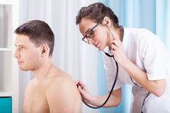 Doctor auscultating patient Royalty Free Stock Photography