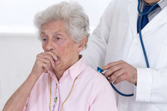 Doctor auscultating patient's lungs. Doctor auscultating senior patient's lungs stock photo