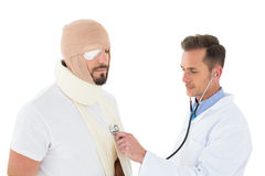 Doctor auscultating patient tied up in bandage with stethoscope Royalty Free Stock Image