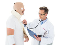 Doctor auscultating patient tied up in bandage with stethoscope Stock Photo