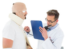 Doctor auscultating patient tied up in bandage with stethoscope Stock Photography