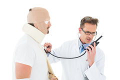 Doctor auscultating patient tied up in bandage with stethoscope Stock Photos