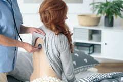 Doctor visiting sick woman. Doctor auscultating sick women using stethoscope during medical visit at home Stock Photo