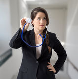 Doctor auscultating with stethoscope against hospital bac Royalty Free Stock Photo