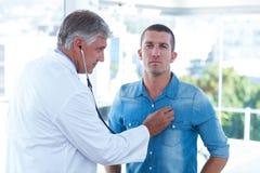 Doctor auscultating su pecho de los pacientes imagen de archivo