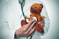 Doctor auscultating a teddy bear with bandages in its head and a Royalty Free Stock Photo