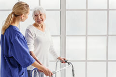 Doctor availing retiree going with gutter frame Stock Image
