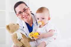 Doctor and baby. A happy female paediatrician doctor and a cute baby in hospital rooms Royalty Free Stock Photo
