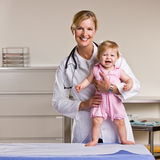 Doctor and baby girl in doctor office. Doctor poses with a baby girl in an examination room Royalty Free Stock Photography