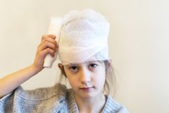 Doctor bandaged the girl`s head stock image
