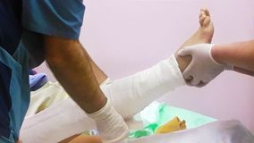 A doctor bandages a broken leg to a patient. Mobile photo stock photos