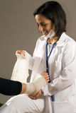 Doctor Bandages a Person's Foot-Vertical. Female Doctor bandages a person's bare foot. She is wearing her mask partially on her face so you can see she is Stock Photo