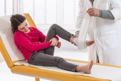 Doctor bandaging foot patient in hospital