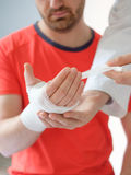 Doctor bandaging the hand of a sport man after an accident Royalty Free Stock Photo