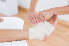 Doctor bandaging her patient ankle Royalty Free Stock Images