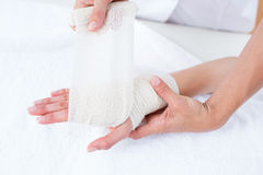 Doctor bandaging her patient wrist Royalty Free Stock Photos