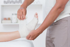 Doctor bandaging his patient ankle Stock Photography
