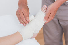 Doctor bandaging his patient ankle Stock Images