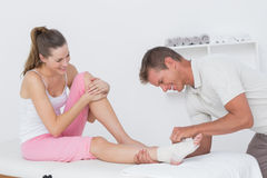 Doctor bandaging his patient ankle Stock Photo