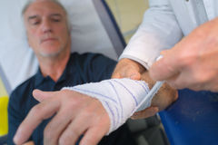 Doctor bandaging patient hand in medical office royalty free stock photography
