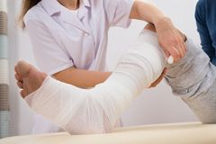 Doctor bandaging patient's leg Royalty Free Stock Image