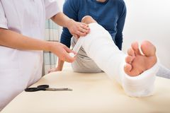 Doctor bandaging patient's leg Stock Photo