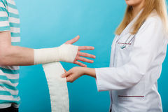 Doctor bandaging sprained wrist. Royalty Free Stock Photography