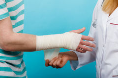 Doctor bandaging sprained wrist. Royalty Free Stock Photos