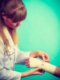 Doctor bandaging sprained wrist. Royalty Free Stock Image