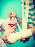 Doctor bandaging sprained wrist. Stock Photo