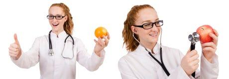 Doctor bastante de sexo femenino con el estetoscopio y la naranja aislados en whi Imagen de archivo