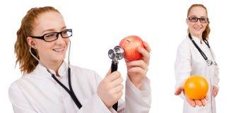 Doctor bastante de sexo femenino con el estetoscopio y la naranja aislados en whi Imagen de archivo libre de regalías