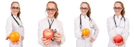 Doctor bastante de sexo femenino con el estetoscopio y la naranja aislados en whi Fotos de archivo