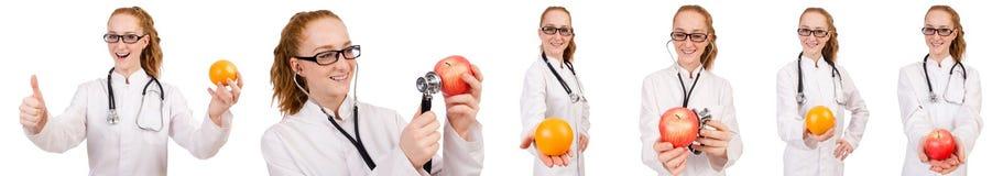 Doctor bastante de sexo femenino con el estetoscopio y la naranja aislados en whi Foto de archivo