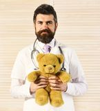 Doctor with beard in white medical coat. Man in surgical uniform with stethoscope on neck and toy. On wooden background. Pediatrician with happy face holds stock photos