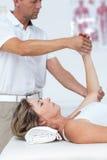 Doctor bending his patient arm Stock Photos