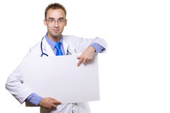 Doctor and blank board. Smiling young male doctor holding blank board and pointing Stock Photo