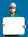 Doctor with a Blank Board. A young woman doctor in a mask holding an empty bill board against a blue background Royalty Free Stock Image